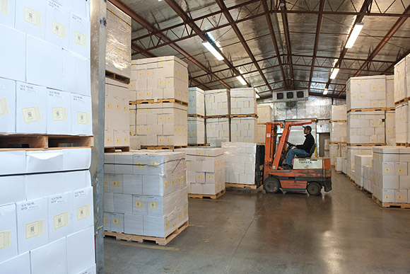 A forklift maneuvers in Navarro's case-goods warehouse, insulated and air-conditioned