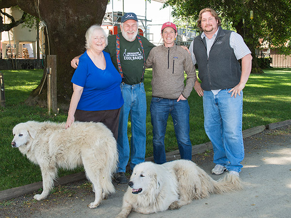 Photo of Bennett-Cahn family with Capo and Pecorina, livestock guardian dogs.