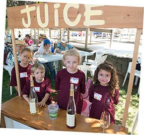 Kids pouring samples of juice at their juice stand during Navarro's annual barrel tasting party