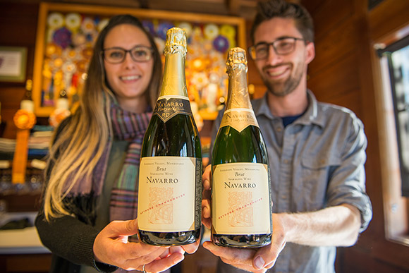 Julia and Tyler, Navarro employees, holding a bottle each of Navarro Brut Sparkling Wine