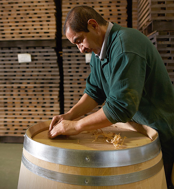 A man from Billon Cooperage assembles a wooden barrel