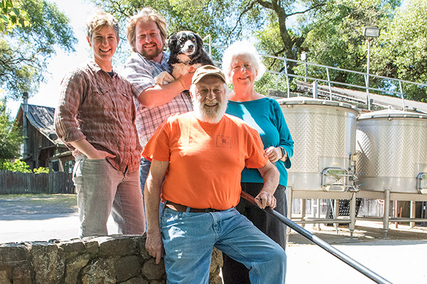 Photo of Bennett-Cahn family in front of open-top wine tanks