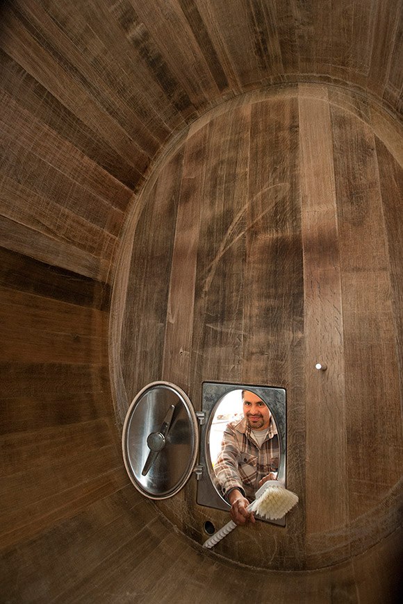 The view from inside a large oak wine oval, Ulises outside with a scrub brush ready to clean it.