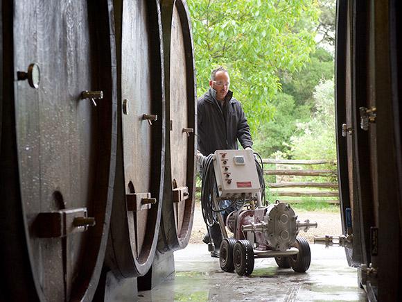Alfredo moving a pump into the cellar with medium sized ovals—about 650 gallons—to rack the wine off its lees.